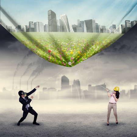 ambiente laboral: Los empresarios tratan de salvar el medio ambiente tirando de una bandera de la nueva ciudad verde Foto de archivo