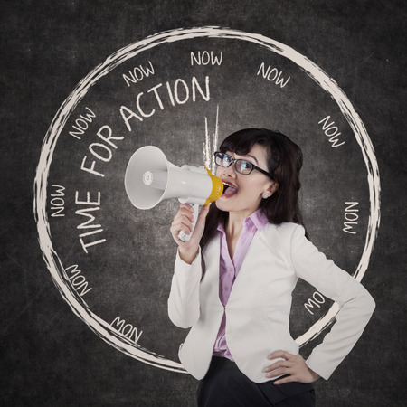 Young businesswoman or teacher announcing an order using megaphone in classroom photo
