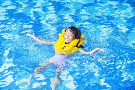 Cute girl playful on the pool while wearing a life jacket. photo
