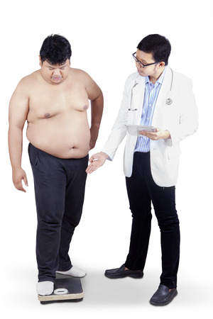 weigher: Doctor measuring the body mass of overweight man with weigher. isolated on white