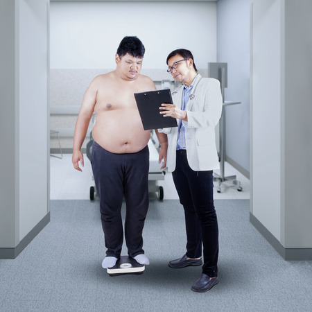 weigher: Doctor measuring the body mass of overweight man with weigher