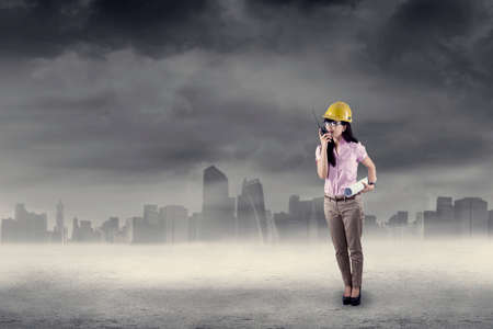 talkie: Woman in hard hat using walkie talkie while holding blueprint. shoot outdoors Stock Photo