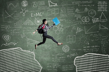 Female student jumping in classroom through gap on the blackboard Stock Photo