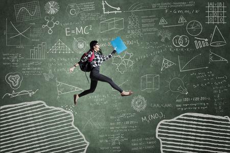 estudiando: Mujer estudiante saltando en el aula a través del hueco en la pizarra