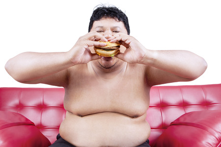 Fat man eating hamburger seated on sofa at home photo