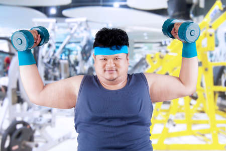 Fat man exercise in fitness center by lifting two dumbbells photo