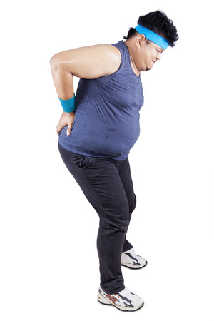 Fat man having back pain while exercising. isolated on white background photo