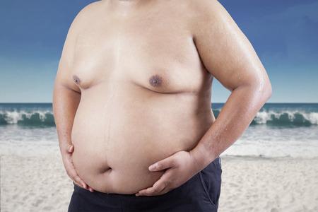 obeso: Hombre agarrando su grasa en el estómago. disparar a la playa Foto de archivo