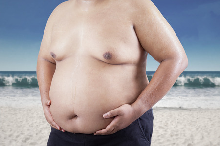 Man grabbing his fat on the stomach. shoot at the beach photo