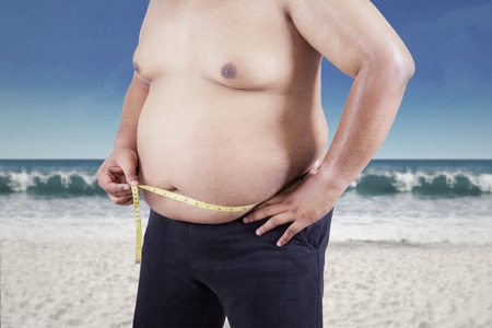Fat man measuring his stomach size. shoot at beach photo