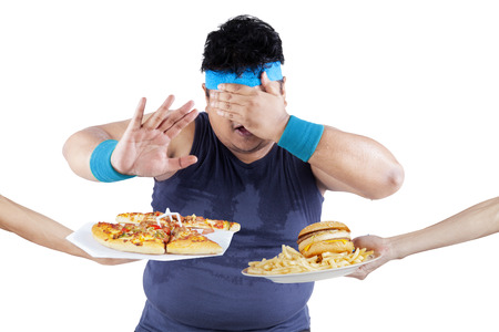 comida chatarra: Hombre gordo rechazo a comer comida chatarra. Aislado en el fondo blanco