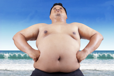 Fat man with big stomach standing on beach photo