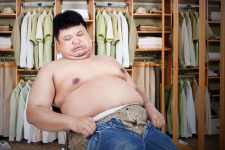 Obese man trying to wear his old jeans photo