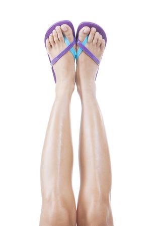 pies sexis: Hermosas piernas femeninas con flip-flops hacia arriba. Aislado en el fondo blanco