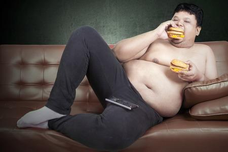 sit: Greedy fat man eating hamburger while watching tv at home