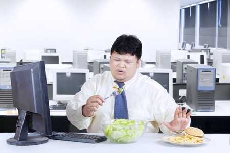 Overweight businessman avoid junk food and choose to eat salad photo