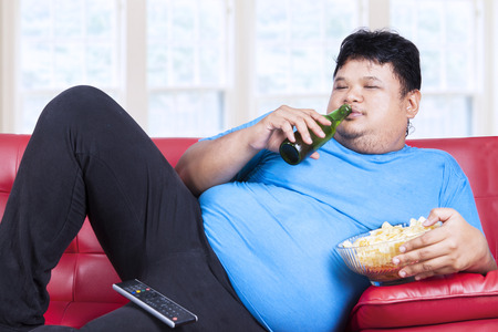 Overweight man sitting lazy on sofa while drinking beer and eat snack