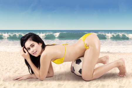 brazil beach swimsuit: Young sexy woman with a soccer ball posing at the beach Stock Photo