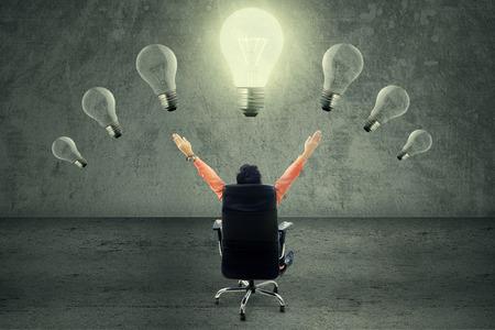 executive chair: Successful businessman sitting on chair under lightbulb Stock Photo