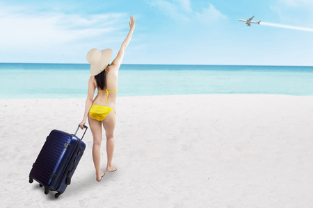 sexy asian girl: Beautiful asian woman with suitcase and swimsuit at the beach
