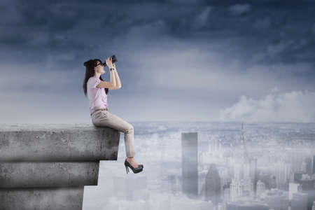 seeking solution: Young woman using binoculars on rooftop for looking her vision