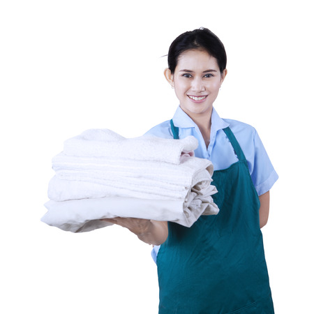 Smiling young cleaning lady holding towels isolated on white photo