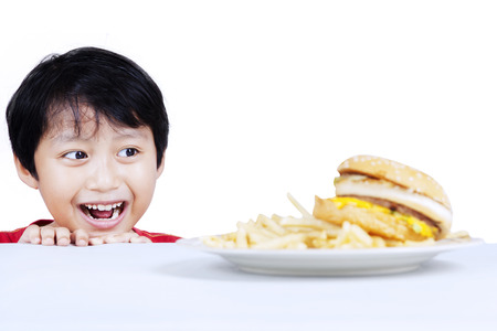 Hungry boy looking at beef burger. isolated on white background photo