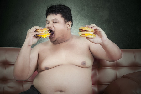 Greedy fat man eating hamburger while watching tv at home photo