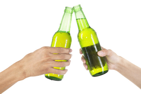 Closeup of hands toasting with bottles of beer