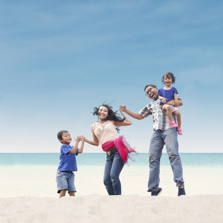 Happy Asian family at the beach photo