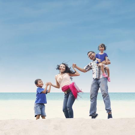 Happy Asian family at the beach photo