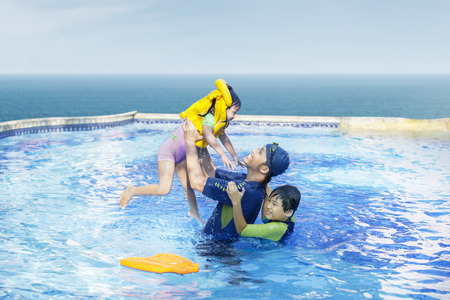 Happy family playing on the swimming pool together photo