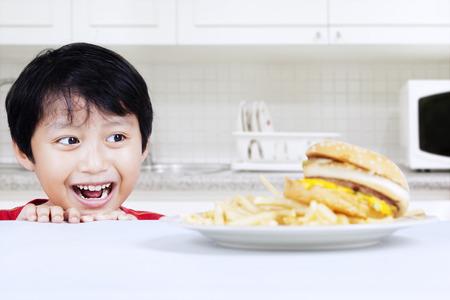 Muchacho hambriento mirando hamburguesa de carne en la cocina Foto de archivo