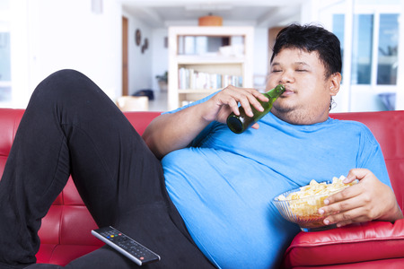 Overweight man sitting lazy on sofa while drinking beer and eat snack photo