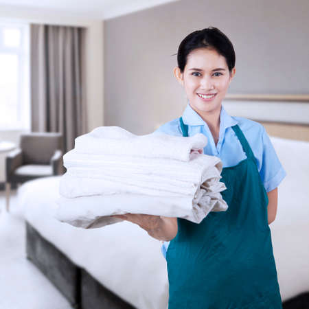 housekeeping: Smiling young cleaning lady holding towels in the hotel room Stock Photo
