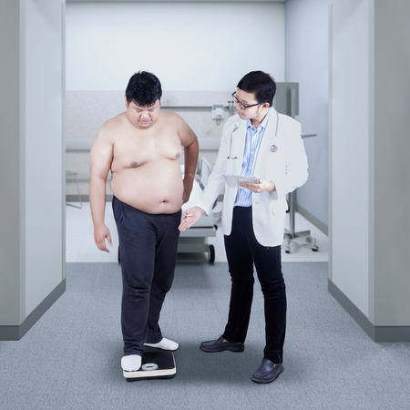 weigher: Doctor measuring the body mass of overweight man with weigher. Stock Photo
