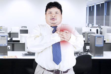 Obesity businessman getting heart attack in office photo