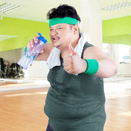 asian bodybuilder: Overweight man drinking water while showing thumb up in fitness center