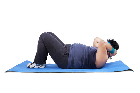 Overweight man working out on mattress. Isolated on white background photo