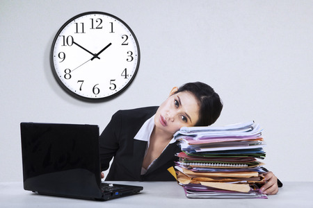 workload: Portrait of overworked businesswoman take a rest on a pile of documents Stock Photo