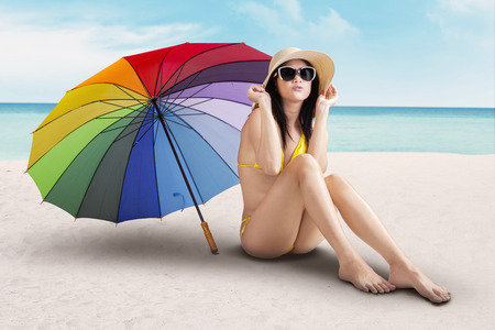 Portrait of model with colorfull umbrella at beach