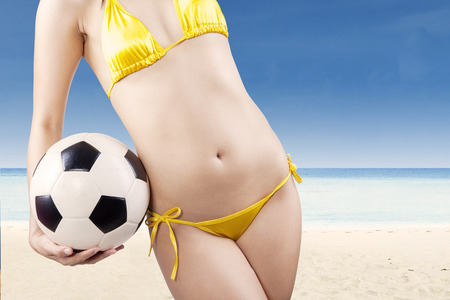 Woman hands holding soccer ball at beach photo