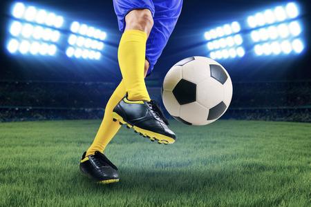 patada: Jugador de fútbol pateando la pelota en el campo en la noche