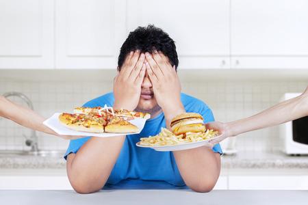 Uomo grasso rifiutando di mangiare cibo spazzatura. Spara a casa in cucina