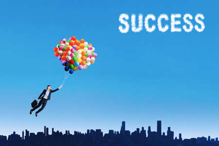pursue: Businesswoman flying with balloons over cityscape to get success Stock Photo