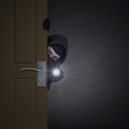 A burglar sneaking in a open house door during a break and enter past security locks and alarms,