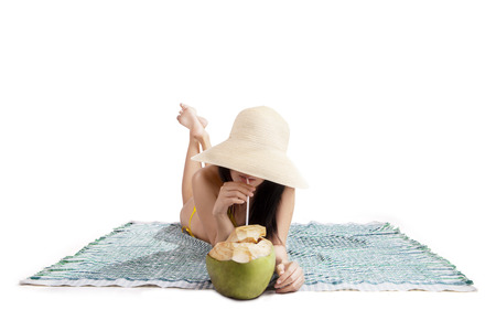 Beautiful woman drinking a coconut water isolated on white photo