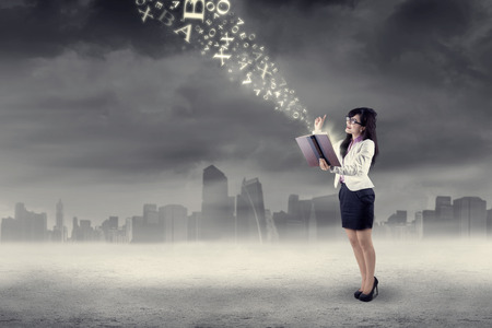 Businesswoman having an inspiration and looking at flying alphabet photo