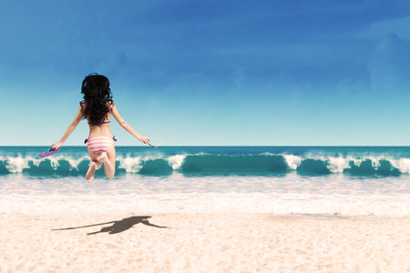 Back view of young woman in bikini jumping at beach while holding sandals and sunglasses photo