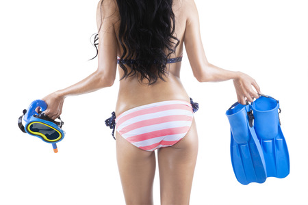 Vacation and beach holidays travel concept. Woman walking with snorkeling equipment. photo